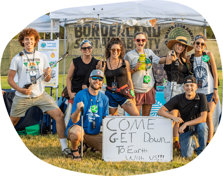 """group at music festival with whiteboard that reads """"come get down to earth with us"""""""
