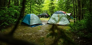 two camping tents and car in woods