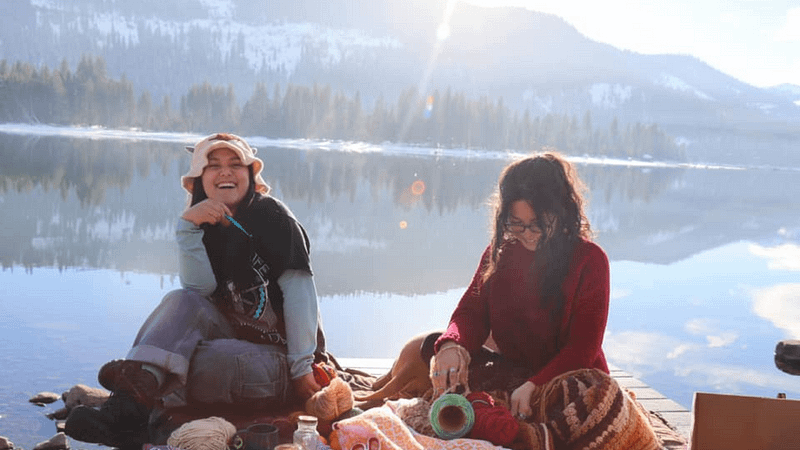 two women sitting on dock in front of lake