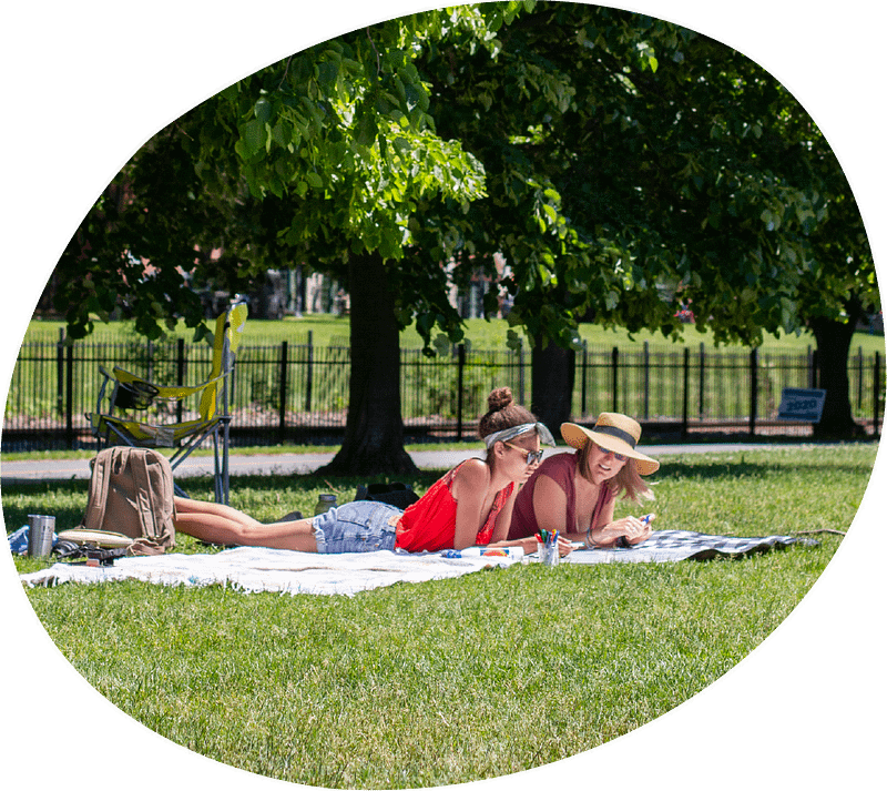 two women laying on a blanket in a park