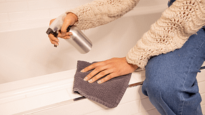 person cleaning bathtub with spray bottle and towel