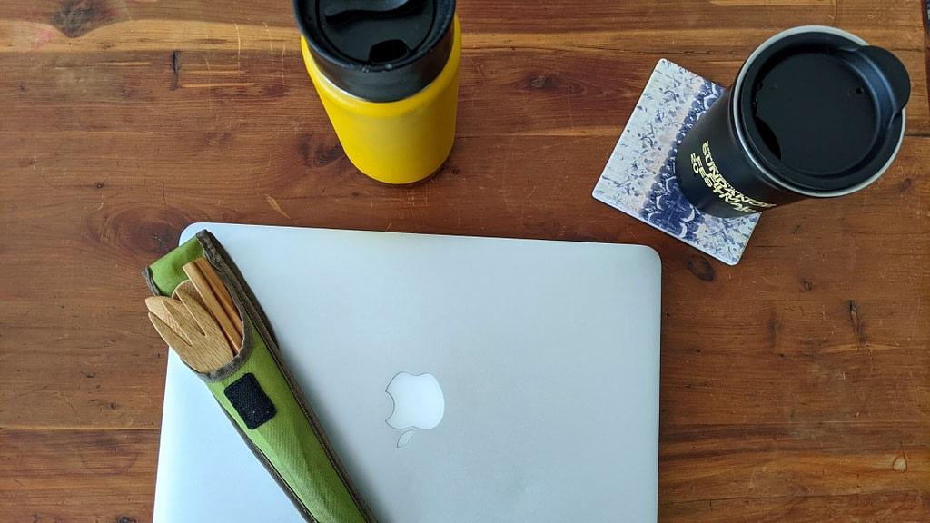 reusable utensils, water bottle, and coffee mug on desk